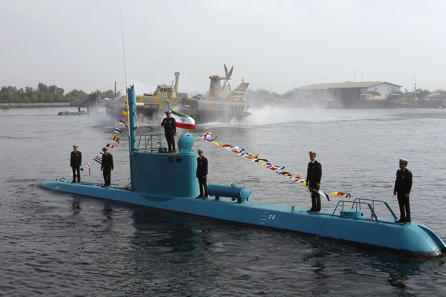 An Iranian Qadir light submarine and a hovercraft move in the Gulf waters in southern port of Bandar Abbas on November 28, 2012, after they were launched in an official ceremony. Iran boosted its naval power in Gulf waters after a new missile launching vessel and two light submarines joined its Navy fleet. AFP PHOTO/MEHR NEWS/AHMAD JAFARI